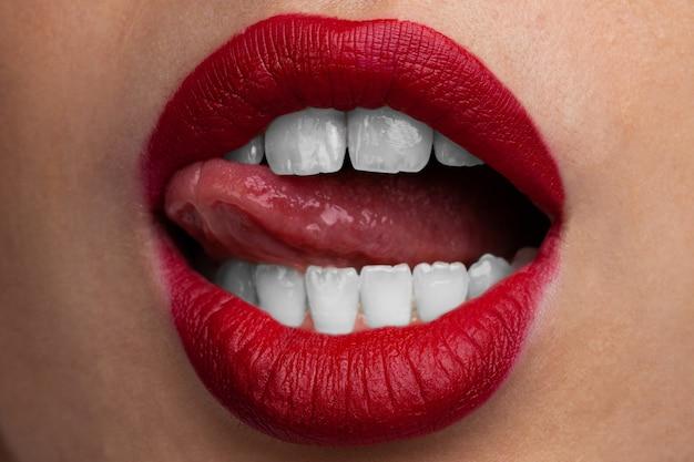 Labbra rosse sexy del primo piano della giovane donna.