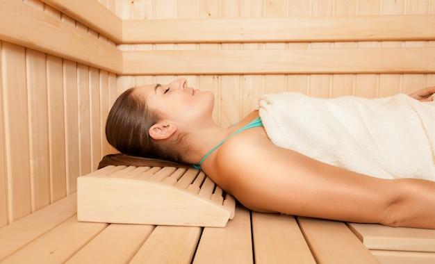 Sexy donna rilassata sdraiata sulla panchina alla sauna