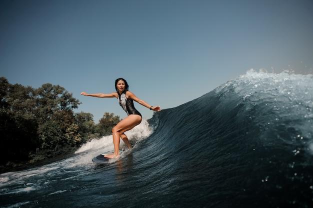 Donna esile sexy del brunette che pratica il surfing a bordo giù l'acqua blu