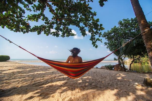 La ragazza esile sexy gode di relax su un'amaca sulla riva di un'isola tropicale paradisiaca.
