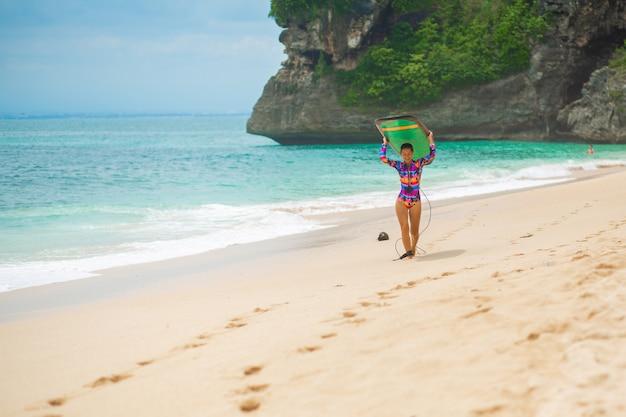 Ragazza sottile sexy con tavola da surf sulla spiaggia di sabbia tropicale.
