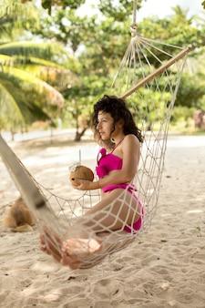 La donna esile sexy gode di di rilassarsi su un'amaca sulla riva di un'isola tropicale paradisiaca.