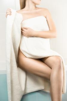 Sexy donna magra seduta sul lato della vasca da bagno e che si copre con un asciugamano