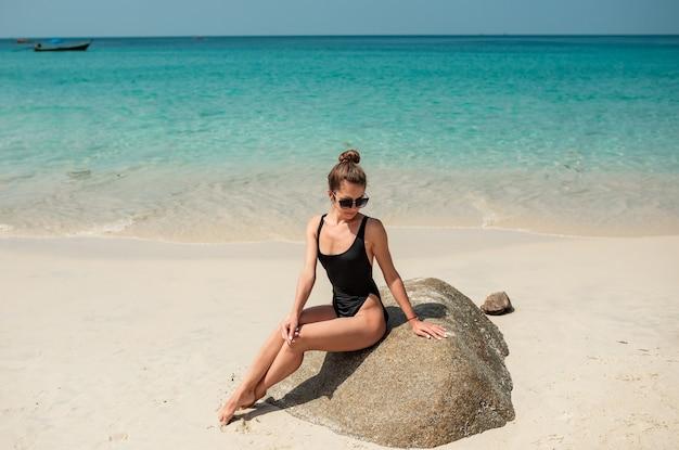 Sexy ragazza in forma abbronzata in bikini nero sulla superficie dell'oceano blu
