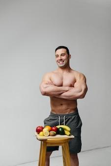 Ragazzo vegano sexy con un torso nudo in posa accanto alla frutta. dieta. dieta sana.