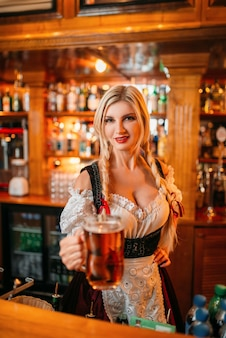 La cameriera sexy ha offerto un boccale di birra schiumosa fresca al bancone del pub.