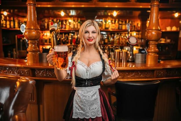 Cameriera sexy tiene due boccali di birra fresca nel pub.