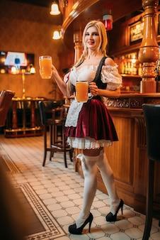 Cameriera sexy in uniforme retrò tiene due boccali di birra fresca nel pub.