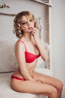 Donna dai capelli ondulati sexy in lingerie rossa con la mano sulle labbra.