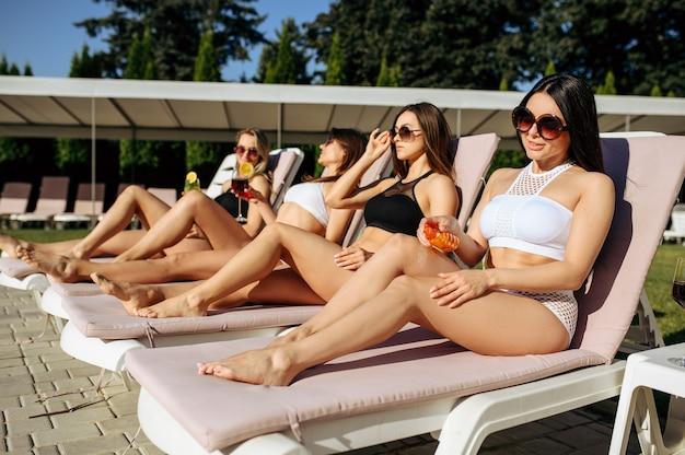 La donna sexy applica lo spray abbronzante sul lettino, prendendo il sole. belle ragazze si rilassano a bordo piscina in una giornata di sole, vacanze estive di amiche attraenti