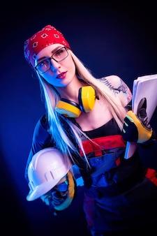 L'architetto donna sexy che tiene i progetti e indossa un casco. alla luce del neon
