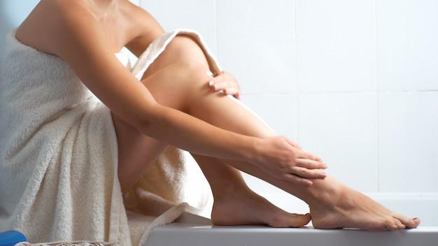Donna sexy in asciugamano da bagno che si siede sul bordo del bagno e massaggia le gambe ei piedi.