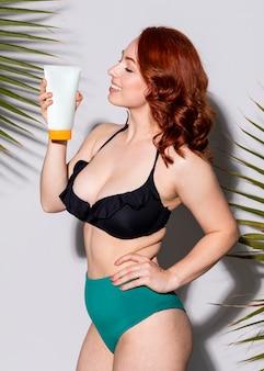 Donna sexy in bikini con in mano un tubetto di crema solare