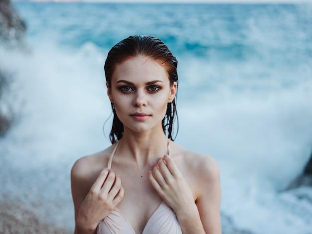 Donna sexy in bikini modello costume da bagno capelli bagnati trasparente oceano acqua schiuma bianca.