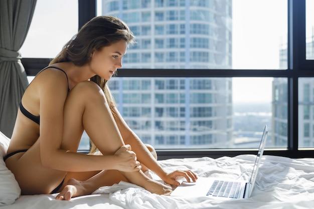 Donna sexy in lingerie nera sdraiata sul letto e usando il portatile