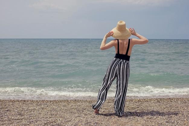 Donna sexy in costume da bagno nero, pantaloni a righe e occhiali da sole cammina sulla spiaggia in riva al mare in estate
