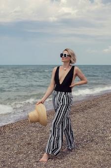 Donna sexy in costume da bagno nero, pantaloni a righe e occhiali da sole cammina sulla spiaggia