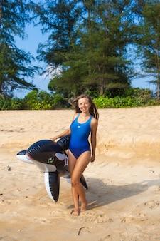 Donna sexy in costume da bagno blu sulla spiaggia con il giocattolo gonfiabile