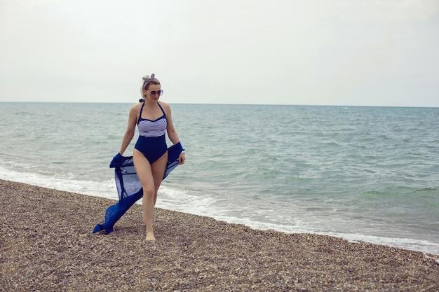 Donna sexy in costume da bagno blu e occhiali da sole cammina sulla spiaggia