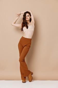 Donna sexy in reggiseno e pantaloni marroni scarpe tacco alto sfondo beige gesticolando con le mani
