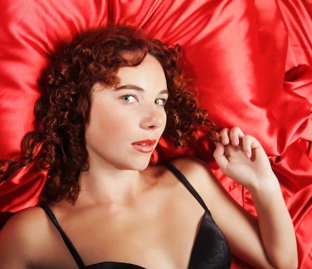 Donna sexy che pone sul letto