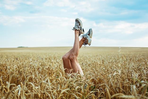 Gambe sexy della donna sul concetto di vacanza estiva del fondo del campo di grano e del cielo blu che si rilassa su un ...