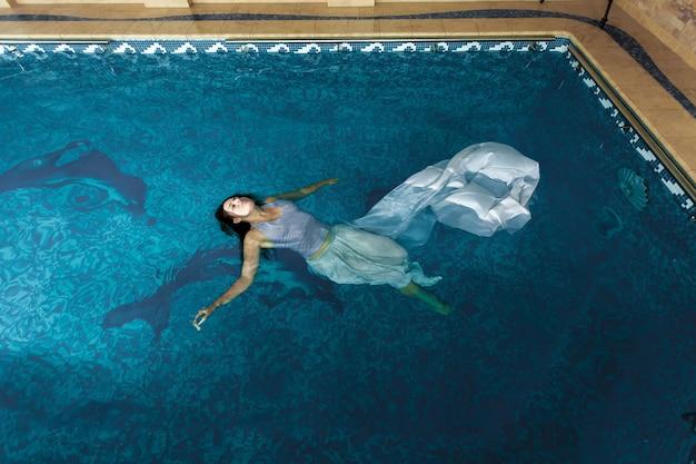 Donna sexy in abito lungo bianco che nuota sulla superficie dell'acqua in piscina