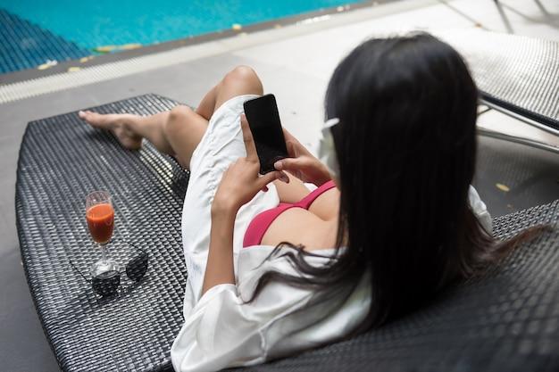 Donna sexy gioca smartphone in piscina