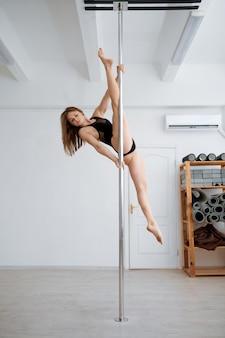 Donna sexy sull'allenamento di pole-dancing in classe. le ragazze con un corpo perfetto mostrano uno stretching eccellente