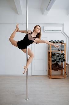 Donna sexy sull'allenamento di pole-dancing in classe