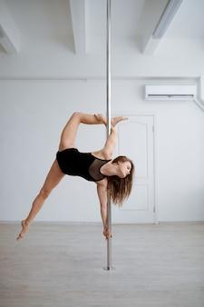 Donna sexy pratica pole dance, allenamento in classe