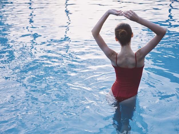 La donna sexy in costume da bagno rosso tiene le sue mani sopra la sua testa nella vista posteriore della piscina
