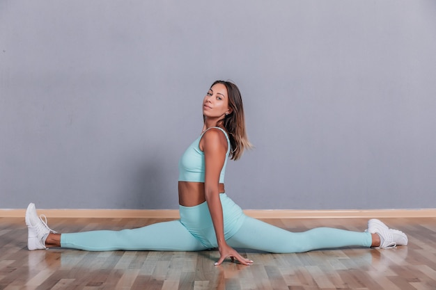 Donna sexy che si siede sul pavimento in spago in uno studio fotografico grigio.