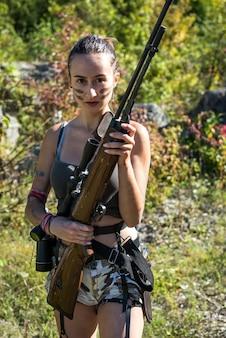 Soldato sexy della donna che tiene un fucile che osserva via nella natura. guerriera