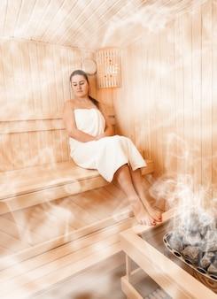 Donna sexy nella sauna finlandese al vapore seduta con gli occhi chiusi