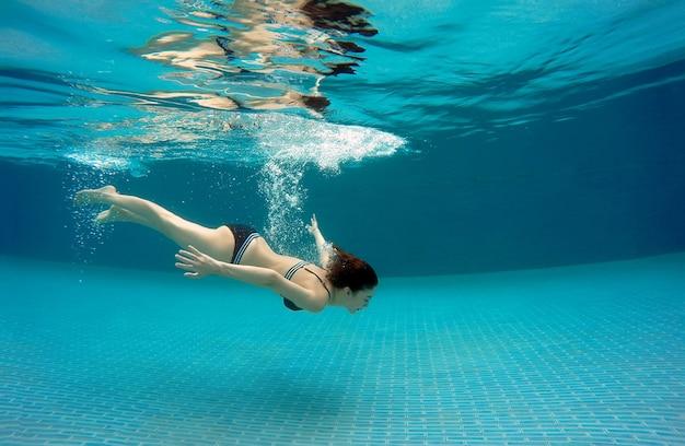 Donna sexy che nuota sott'acqua in piscina in un giorno d'estate