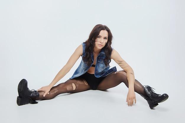 Donna sexy in calzamaglia strappata e pose di giacca di jeans