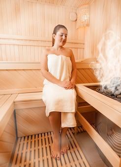 Donna sexy in asciugamano rilassante nella sauna finlandese al vaporeed