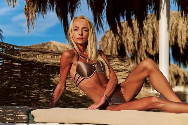 Bikini da portare della donna sexy che si siede sul lettino sotto l'ombrello del baldacchino di paglia in spiaggia