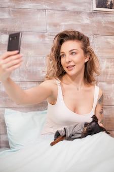 Donna sexy che indossa un pigiama che si fa un selfie con il suo cane a letto di notte.