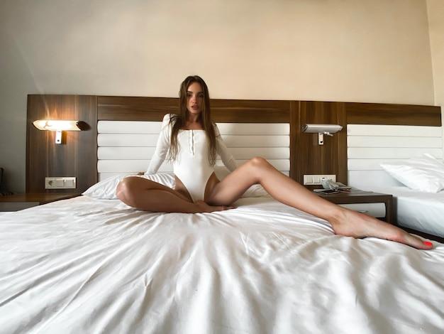 Donna sexy in tuta bianca in posa su un letto nella camera d'albergo