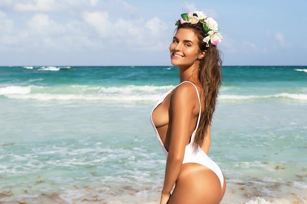 Donna sexy in costume da bagno bianco è in posa sulla spiaggia