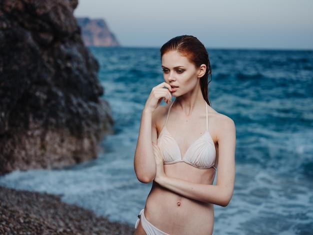 Donna sexy in costume da bagno bianco vicino al mare e la spiaggia di schiuma oscilla la natura