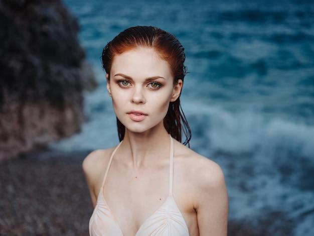 Donna sexy in costume da bagno bianco vicino al mare e la spiaggia di schiuma oscilla la natura.