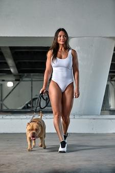 Donna sexy con una figura atletica con cane bullo americano per le strade della città.