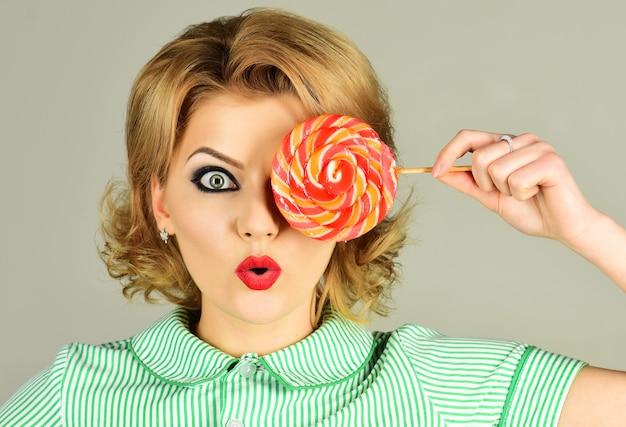 Donna sexy con lecca-lecca colorato. ragazza pinup con caramelle. cibo dolce.
