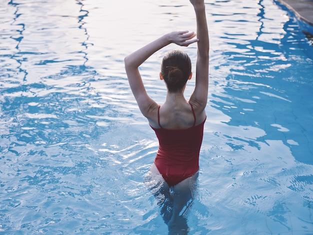La donna sexy con le braccia alzate sta in piscina in una vista posteriore del costume da bagno rosso