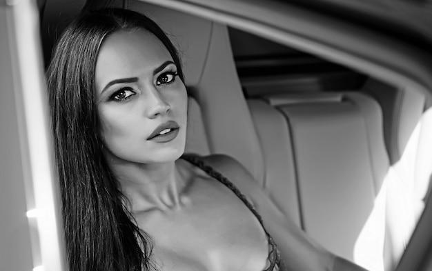 Fronte della donna sexy in auto di lusso. ritratto di giovane ragazza di moda glamour sexy con bei capelli lunghi