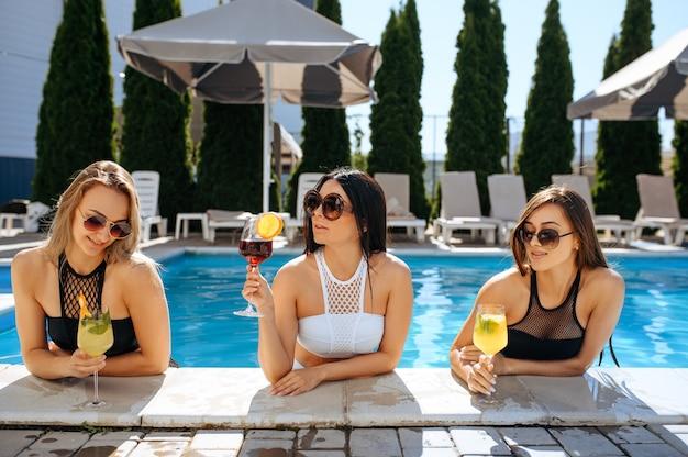 Donne sexy bevono cocktail in piscina all'aperto. belle ragazze in occhiali da sole si rilassano a bordo piscina in una giornata di sole, vacanze estive di amiche attraenti