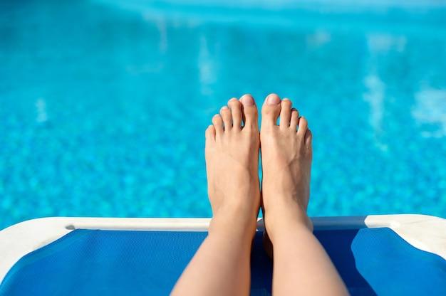 Chiodi di pedicure gambe donne sexy che spruzzano nella piscina estiva di nuoto tropicale.